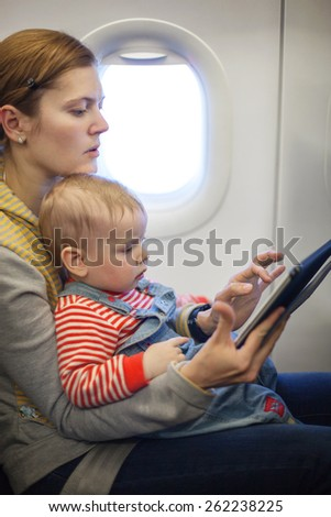 Caucasian mother and toddler son using tablet pc during while on board of airplane - stock photo