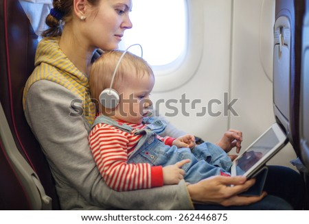 Caucasian mother and toddler son using tablet pc while on board of airplane - stock photo