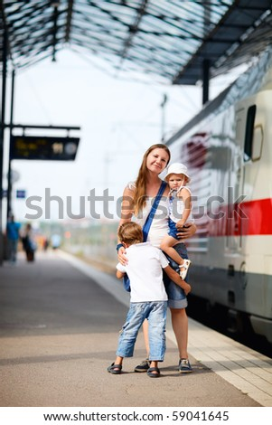Caucasian mother and two kids waiting for train on railway station platform - stock photo