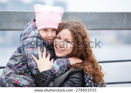 Caucasian mother embracing daughter while walking street, head and shoulders portrait - stock photo