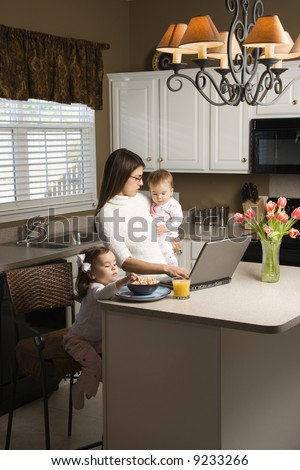 Caucasian mother holding baby  and typing on laptop computer with girl eating breakfast in kitchen. - stock photo