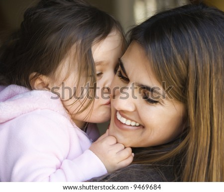 Caucasian mother holding daughter kissing her cheek and smiling. - stock photo