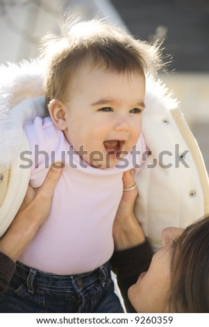 Caucasian mother holding up smiling baby girl. - stock photo
