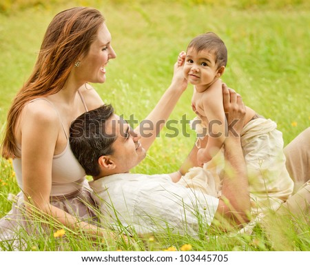 Caucasian Mother with Indian Husband and Baby Son Happy in Long Grass - stock photo