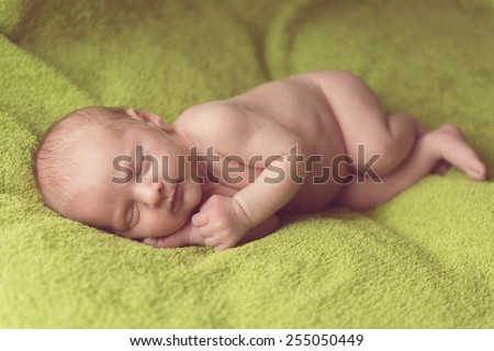 caucasian newborn baby sleeping on green fabric - stock photo
