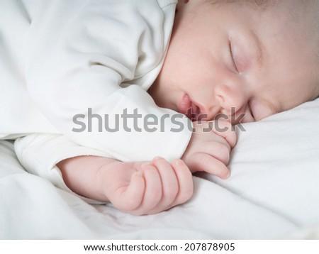 Caucasian newborn baby toddler boy sleeping in his bed - stock photo
