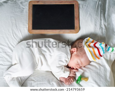 Caucasian newborn baby toddler boy sleeping in his bed with blank chalkboard - stock photo