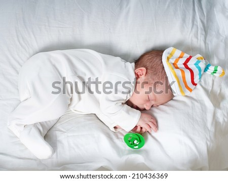 Caucasian newborn baby toddler boy sleeping in his bed with nipple - stock photo