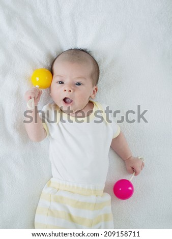 Caucasian newborn baby toddler boy sleeping in his bed with toys