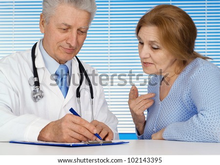 Caucasian nice old doctor with a patient on a light background - stock photo