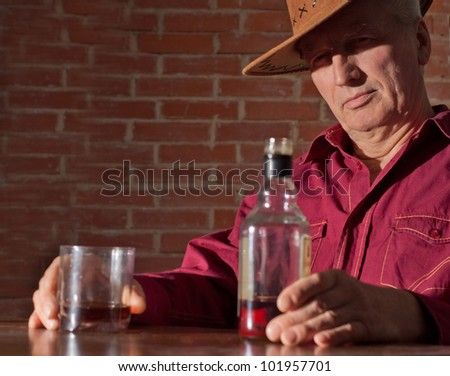 Caucasian old male with a nice bottle sitting on a dark background - stock photo