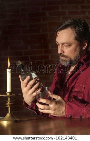 Caucasian old man with a nice bottle sitting on a dark background - stock photo