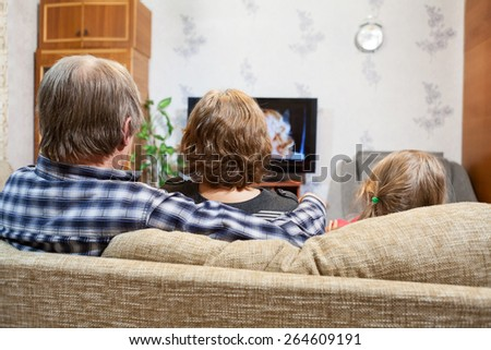 Caucasian parents and daughter sitting on the couch and watching tv, rear view - stock photo
