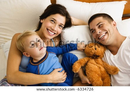 Caucasian parents and toddler son lying in bed smiling. - stock photo