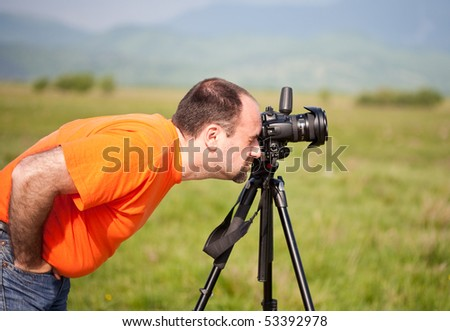 Caucasian photographer taking pictures of the landscape in a sunny day - stock photo