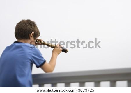 Caucasian pre-teen boy leaning on railing looking through telescope. - stock photo