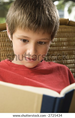 Caucasian pre-teen boy reading book.