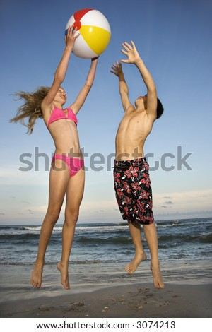 Caucasian pre-teen girl and boy playing with beachball on beach.