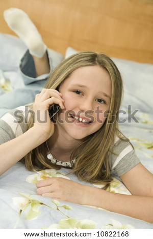 Caucasian preteen girl laying in bed talking on a cell phone - stock photo