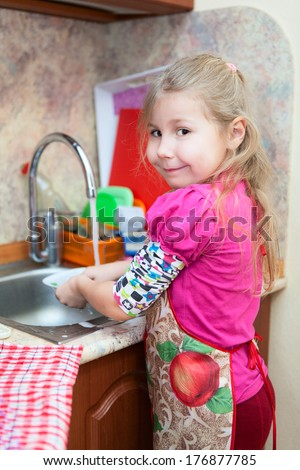 Caucasian pretty young girl in the kitchen washing dishes - stock photo