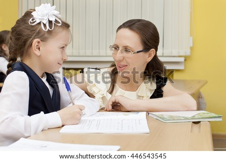 Caucasian primary school teacher and pupil sitting at a desk. Girl writes in a notebook. The teacher looks at her and smiles. Horizontal color image. - stock photo