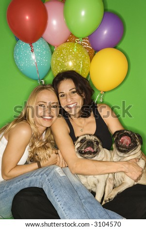 Caucasian prime adult and young adult females with small dogs and festive balloons. - stock photo