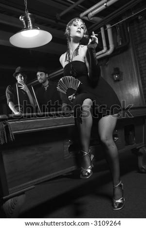Caucasian prime adult female standing in front of pool table with two Caucasian prime adult men in background. - stock photo