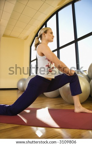 Caucasian prime adult female stretching at gym. - stock photo