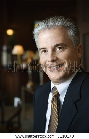 Caucasian prime adult male businessman in hotel lobby. - stock photo