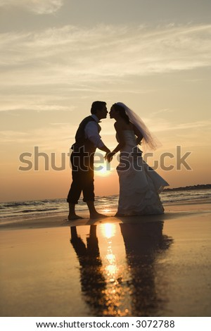 Caucasian prime adult male groom and female bride holding hands and kissing barefoot on beach at sunset.
