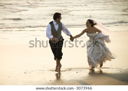 Caucasian prime adult male groom and female bride running barefoot on beach. - stock photo