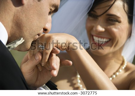 Caucasian prime adult male groom kissing hand of female bride. - stock photo