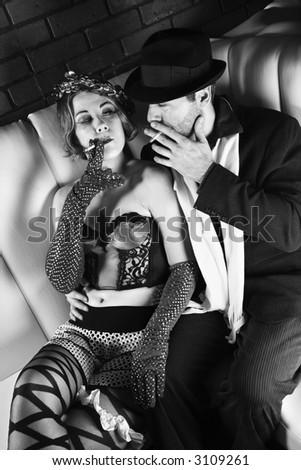 Caucasian prime adult male in retro suit sitting with Caucasian prime adult female in retro wear. - stock photo