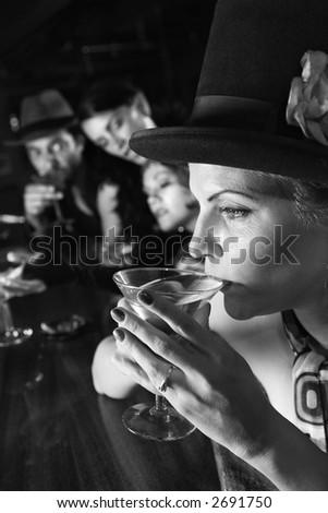 Caucasian prime adult retro female sitting at bar drinking martini. - stock photo