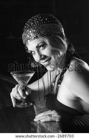Caucasian prime adult retro female sitting at bar with martini looking at viewer. - stock photo