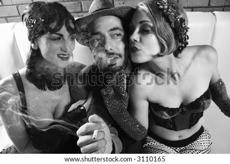 Caucasian prime adult retro male sitting between two Caucasian prime adult retro females. - stock photo