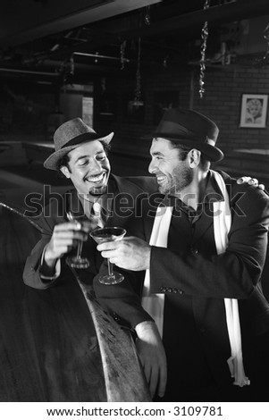 Caucasian prime adult retro males sitting at bar drinking.