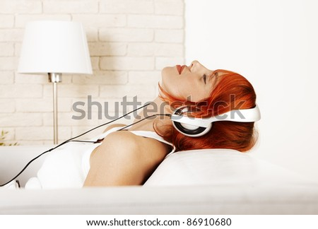 Caucasian redhead woman wearing headphones and listening music