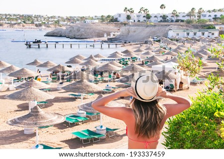 Caucasian resting girl is standing and enjoying view  of ocean and beach with parasoles. Happy relaxing female model in red bikini and white hat. Summer vacation concept (Sharm El Sheikh, Egypt). - stock photo