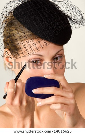 caucasian retro-styled model applying cosmetics on her face - stock photo