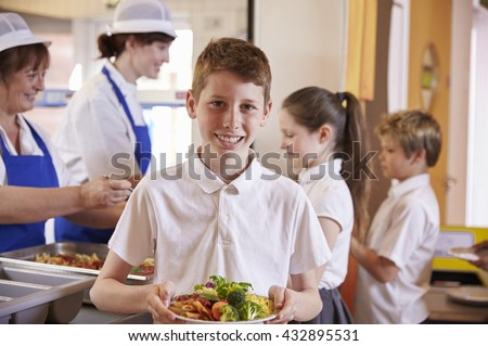 Caucasian schoolboy holds plate of food in school cafeteria - stock photo