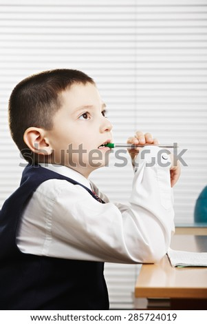 Caucasian schoolboy in formal wear biting pen and looking sideways while sitting at the desk - stock photo