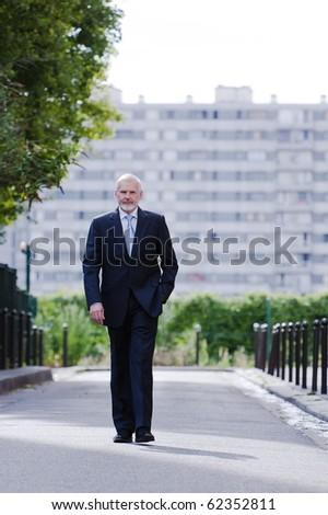 caucasian senior businessman walking confident - stock photo