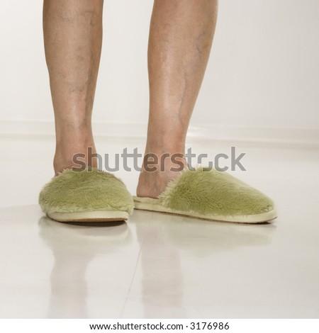Caucasian senior female feet wearing green bedroom slippers. - stock photo