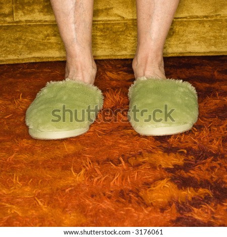 Caucasian senior female feet wearing green bedroom slippers on carpet. - stock photo