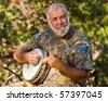 Caucasian Senior Man Playing the Banjo Outdoors. - stock photo