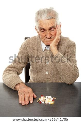 Caucasian senior man taking a huge bunch of pills - stock photo