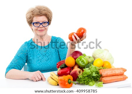 Caucasian senior woman holding two tomatoes in hand while sitting near fresh fruit and vegetables, isolated on white background - stock photo