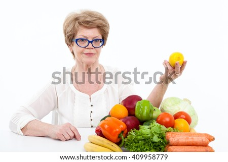 Caucasian senior woman showing lemon in hand while sitting near fresh fruit and vegetables, isolated on white background - stock photo