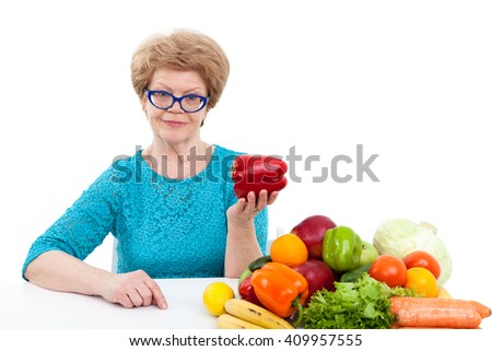 Caucasian senior woman showing red sweet pepper in hand while sitting near fresh fruit and vegetables, isolated on white background - stock photo